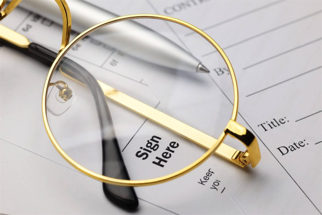gold-framed-glasses-on-top-of-papers