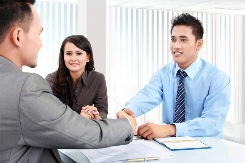 Business owners and financial consultant shaking hands over a table