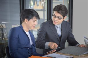 two men in business suits having a discussion while holding a tablet
