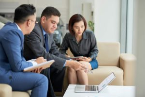 three people in business suits discussing about business loan options in singapore