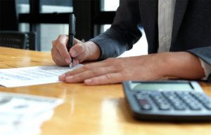An individual signing a contract, with a calculator on the table