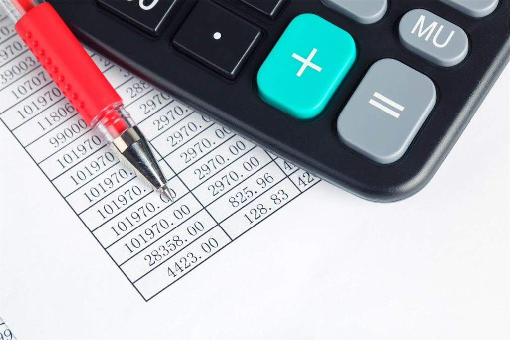 A financial report, with a red pen and a calculator on top of it