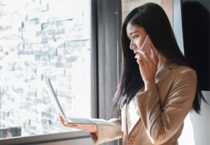 a businesswoman calling at the window while holding a laptop