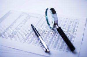 a pen and a magnifying glass on top of a financial report