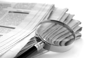magnifying-glass-lying-on-top-of-a-stack-of-newspaper