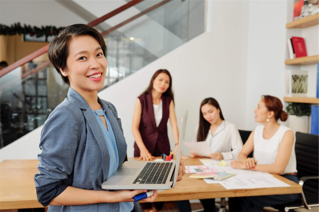 asian-businesswoman-smiling-with-an-opened-laptop