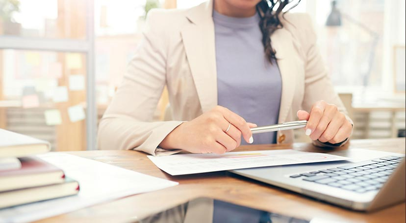 Businesswoman sitting by the desk looking through SME working capital loans in Singapore