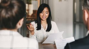:woman-explaining-documents-to-couple-in-a-business-setting