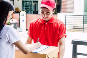 Lady signing parcel delivered by a delivery man