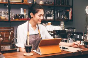 Cafe business owner behind the counter looking to sign a business loan for her business