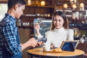 Woman making payment for her cafe meal with a business on a merchant cash advance plan