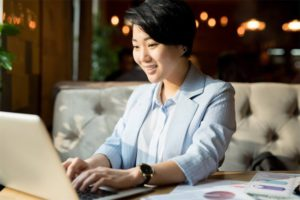Businesswoman on a computer planning on how to use a business loan to prepare for her business reopening