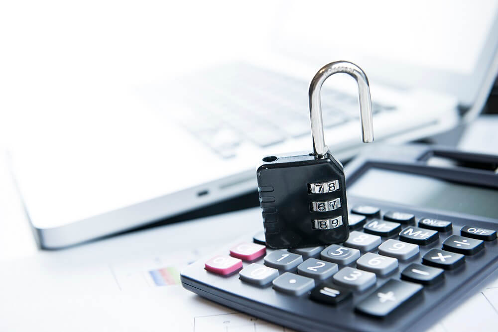 An opened lock with a calculator and laptop, suggesting unlocking opportunities with a business loan