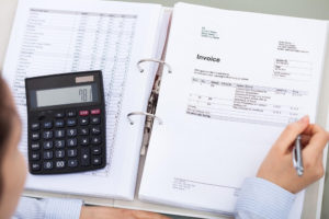 Man calculating invoice slip, thinking of taking up a business loan