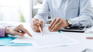 A lender going through payroll business loan contract terms with borrower