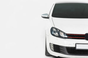Partial shot of a white car against a white background