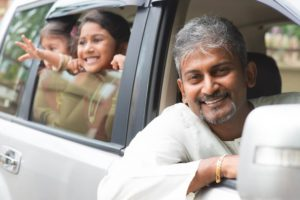 A man and his daughters in a car