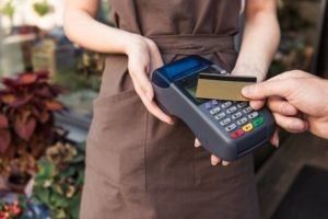 Man making a payment with his credit card at a retail store that uses merchant cash advance plan