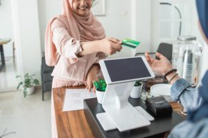 Woman making payment with her credit card at a cafe that uses merchant cash advance plan