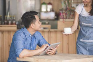 Businessman getting a coffee at a cafe while checking his business loan approval on the tablet