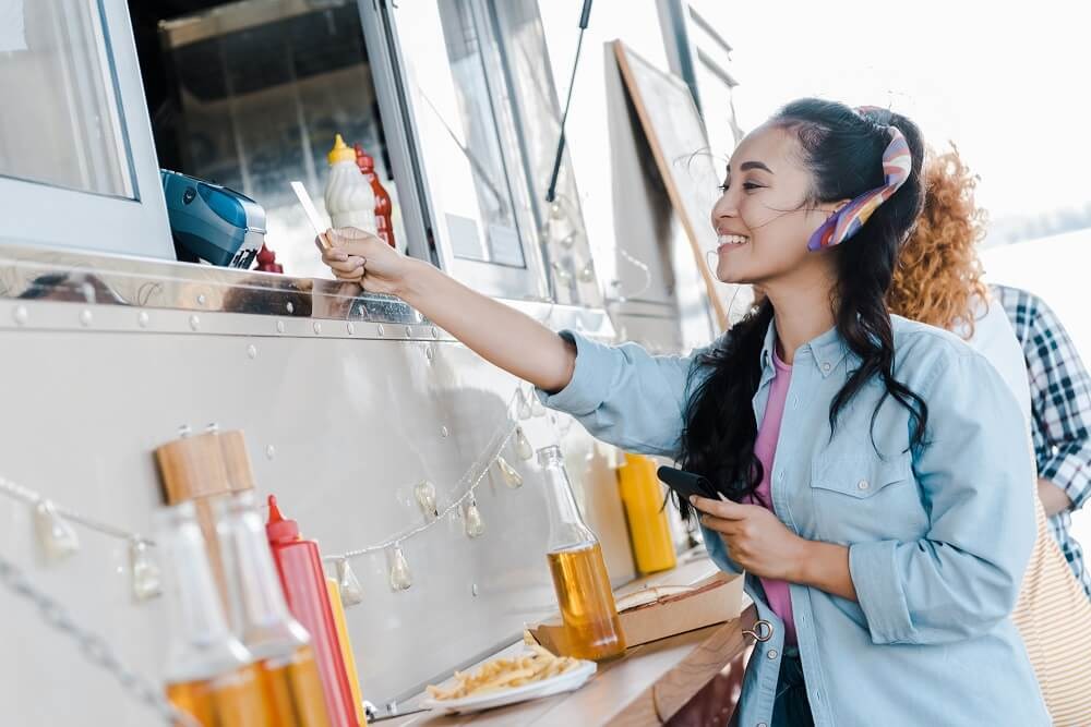 A woman paying for her food at a food truck opened with a business loan