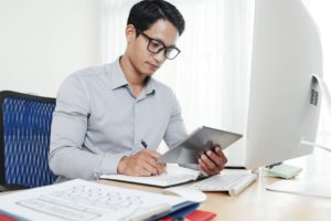 A man looking at his financials and considering to get a business term loan