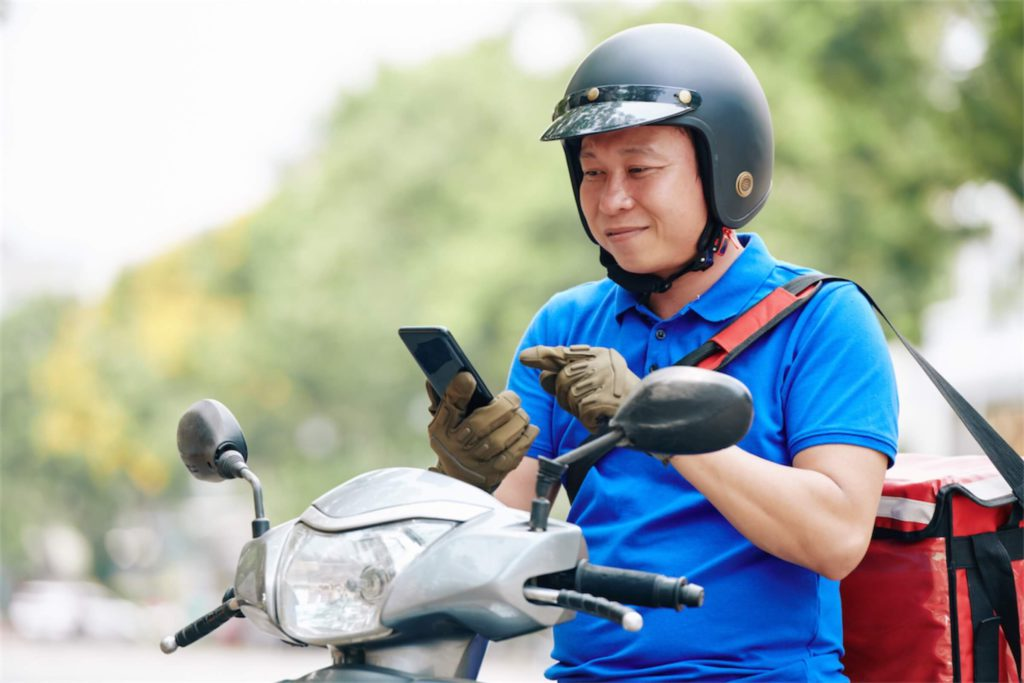 Delivery man accepting a delivery order on his motorcycle funded with a car loan