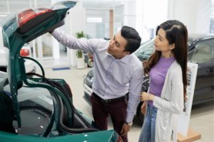 A couple looking at the trunk of a car in an auto dealer and considering to get a car loan