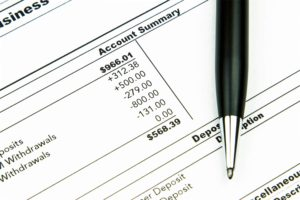 Paper showing bank account summary and deducting monthly car loan payment