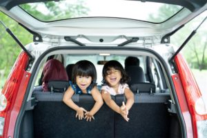 Two children laughing in the boot of a car funded by a car loan