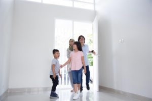Family of four viewing their newly purchased house before getting a car loan