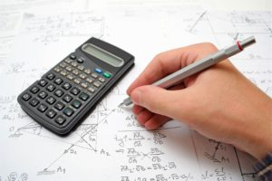 Man calculating his loan tenure with a calculator