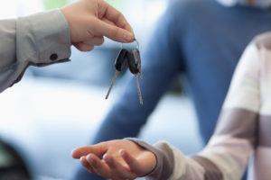 A car dealer passing car keys to a buyer