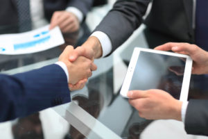 Two individuals shaking hands after signing a hire purchase agreement