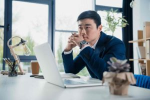 Business owner in front of a laptop thinking of how to make the most of his Covid-19 support loan