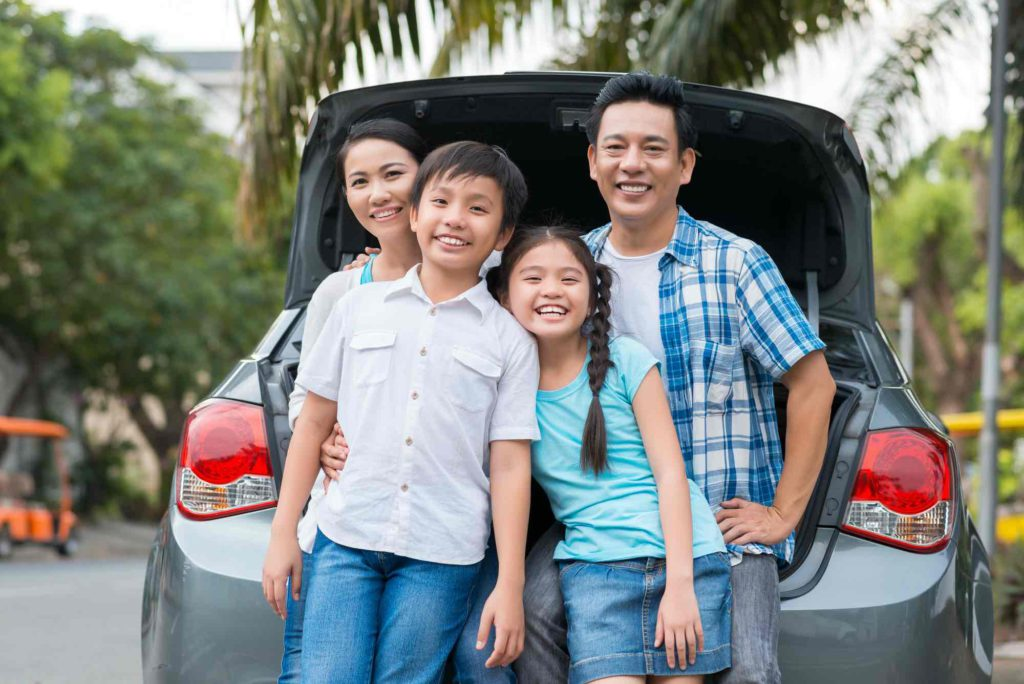Family standing in front of a car with an open boot, bought with an in-house auto loan