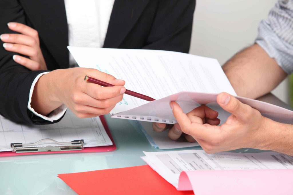 Two individuals going through a legal document