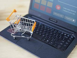 A miniature shopping cart on top of a laptop showing a shopping checkout screen